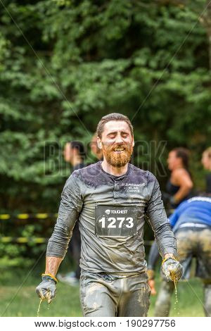Stockholm Sweden - June 03 2017: Close up front view one caucasian man with full beard. Wet dirty and tired after completing a mud obstacle at the annual event Toughest Stockholm. A few people out of focus in the background.