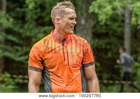 Stockholm Sweden - June 03 2017: Close up front view of a dirty caucasian male athlete in orange sports shirt resting after completing a mud obstacle at the annual event Toughest Stockholm. One person out of focus in the background.