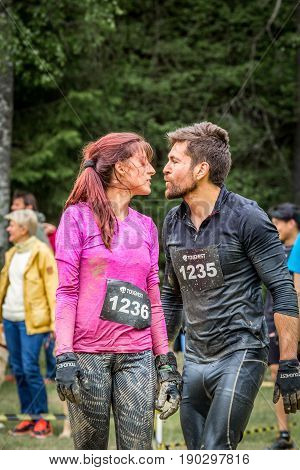 Stockholm Sweden - June 03 2017: Close up front view man and woman wet and dirty after completing a mud obstacle at the annual event Toughest Stockholm. A few people in the background.
