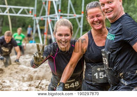 Stockholm Sweden - June 03 2017: Close up front view one caucasian man and two woman in a mud obstacle after completing the course of the annual event Toughest Stockholm. Laughing and smiling People in the background.