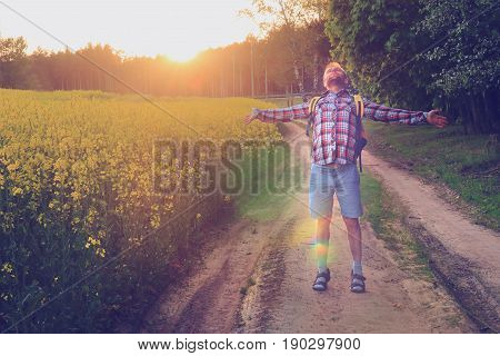 Free state of a happy man on a green grass path at sunset. The young man spread his hands in the direction on background of bright sunlight. A happy journey on foot along the sandy path.