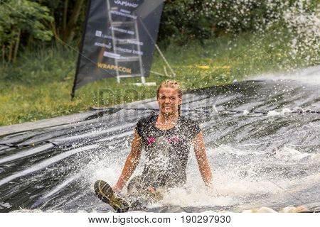 Stockholm Sweden - June 03 2017: Front view of one caucasian woman riding a muddy water slide down hill at an obstacle course to complete the annual event Toughest Stockholm.