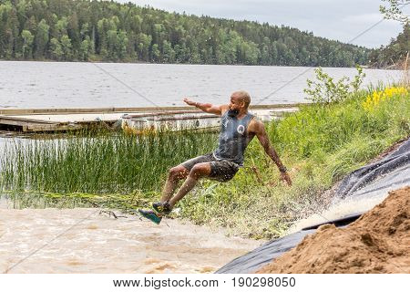 Stockholm Sweden - June 03 2017: Side view of one man in mid air after riding a water slide during the annual event Toughest Stockholm.