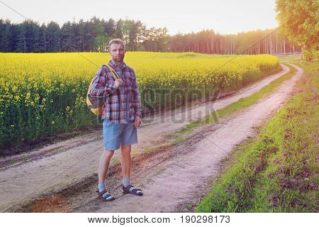A man is walking with a backpack on way to the meadow at sunset in the evening. Bright sunny summer evening outdoors with a tourist on a path in the field