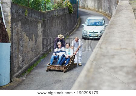 Funchal - March 21: Famous Toboggan Riders Moving Traditional Cane Sledge Downhill On The Streets Of
