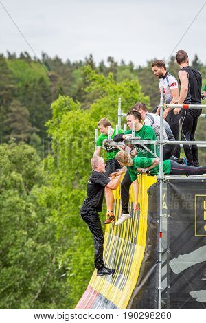 Stockholm Sweden - June 03 2017: Side view with group of young people climbing and standing on an obstacle wall trying to complete the annual obstacle course event Toughest Stockholm.