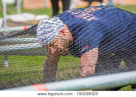 Stockholm Sweden - June 03 2017: Close up of one caucasian man crawling on the ground under a net trying to complete a obstacle course at the annual event Toughest Stockholm.