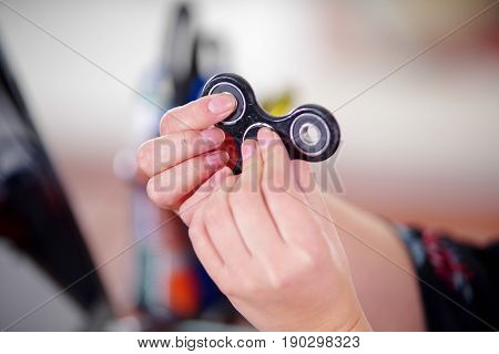 Young woman playing with a popular fidget spinner toy in her hands, on office background.
