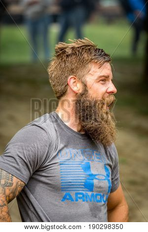 Stockholm Sweden - June 03 2017: Close up profile view of athletic sweaty young man with full beard resting after reaching the finish line in the event Toughest Stockholm. Blurred people in the background.