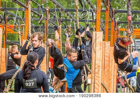 Stockholm Sweden - June 03 2017: Close up of many men and women hanging and climbing trying to get through a obstacle rig during the annual obstacle course event Toughest Stockholm.