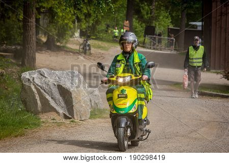 Stockholm Sweden - June 03 2017: Front view of one caucasian female paramedics driving a motor scooter emergency vehicle on a dirt road to assist in outdoor event. A man walking in the background.