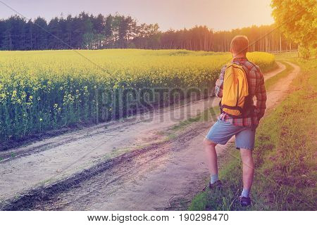 A traveler with a backpack looks forward to the way in the field for a walk. The road goes into the distance of the meadow at sunset, a tourist is walking along the road with a backpack
