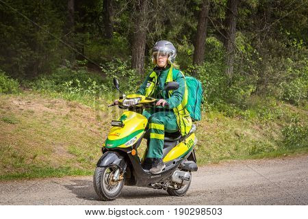 Stockholm Sweden - June 03 2017: Side view of one caucasian female paramedics driving a motor scooter emergency vehicle on a dirt road to assist in outdoor event.