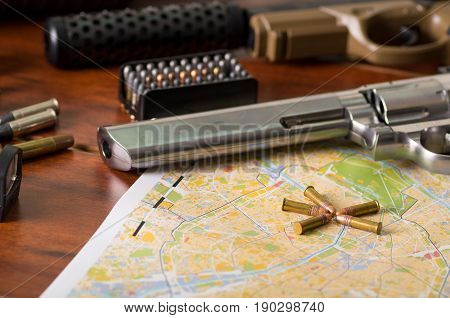 Close up of a shotgun and a revolver, cartridge belt with bullets on a map, on wooden table.