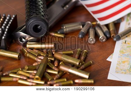 Close up of a shotgun and a revolver, cartridge belt with bullets with part of a blurred United States flag on a map, on wooden table.