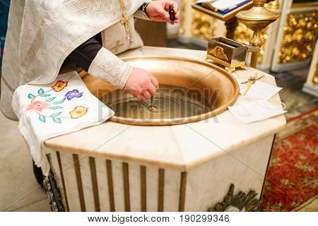 The baptism of Orthodox Christians the priest's hand adds oil to the holy water
