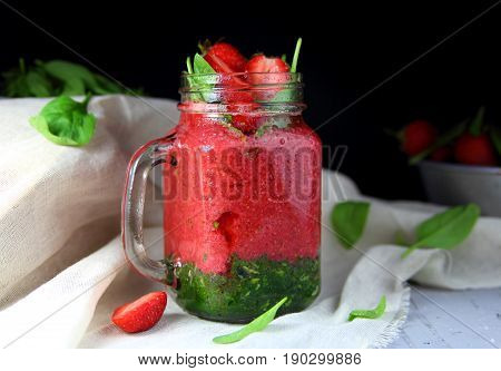strawberry smoothie with spinach in a mug with water drops