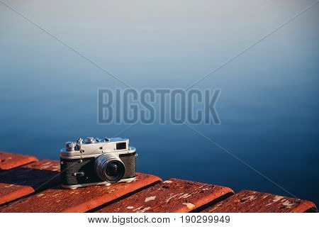Old Vintage Film Photo Camera Lying On Wooden Berth, Dark Blue Water Background. Copy Space