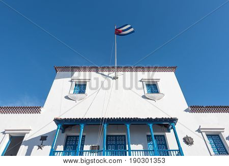 City Halls or Municipal Government colonial building in the Cespedes town square. Worm eye view of white blue building with National flag on a pole.