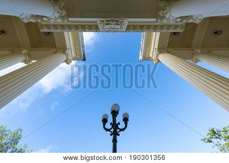 Architectural detail of the entrance at the Jose Marti library. Ant view of colonial building and lamp post across the road with a clear sky above.
