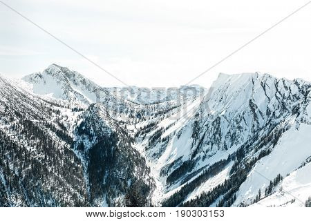 Steep valley between snow covered mountain peaks in alpine scenery with forested slopes in a scenic landscape view