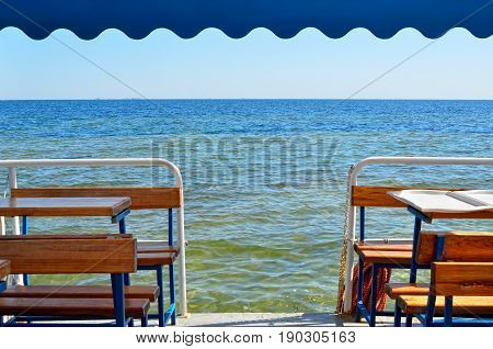 Restaurant on deck of ship against background of sea horizon.