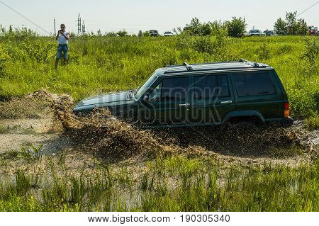 Lviv Ukraine - May 30 2015: Off-road vehicle Jeep Cherokee overcomes the track on of landfill near the city Lviv.