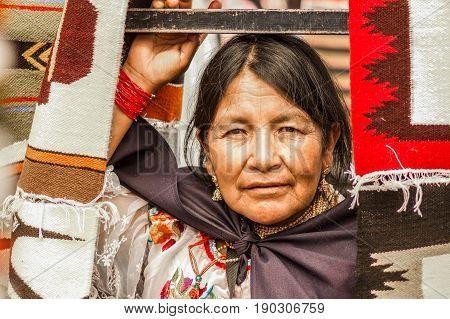 OTAVALO, ECUADOR - MAY 17, 2017: Close up of an unidentified hispanic indigenous woman wearing andean traditional clothing, posing for camera.