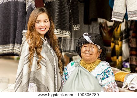 OTAVALO, ECUADOR - MAY 17, 2017: An unidentified hispanic indigenous woman wearing andean traditional clothing and necklace, with a beautiful caucasian woman wearing andean clothes, posing for camera.