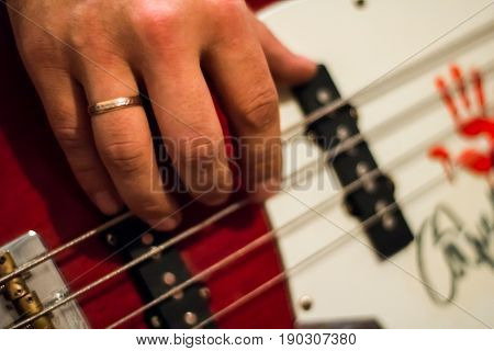 Bass Guitar In Playing Musician Hands Close-up. Focus On Bass Guitar Neck In Player Hands. Unrecogin