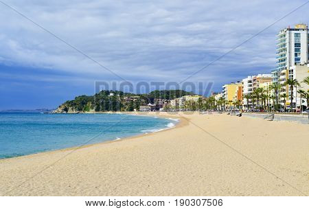 LLORET DE MAR, SPAIN - APRIL 19, 2017: A panoramic view of the Platja de Lloret beach in Lloret de Mar, Spain. It is the main beach in this popular tourist village in the Costa Brava, in Catalonia