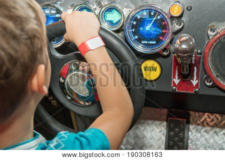 Little boy at the wheel of the car simulator with his back to the camera