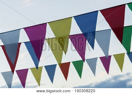 Close-up garland of colorful flags of triangular shape, pennants against blue sky. City street holiday. Modern background, pattern, wallpaper or banner design. Fest, celebration concept