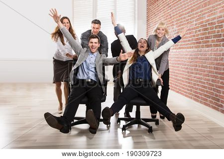 Smiling Businesspeople Playing Together With Swivel Chair In The Office