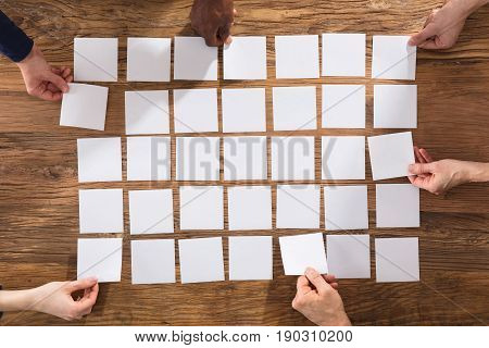 Overhead View Of People Hands Arranging White Papers On Wooden Table