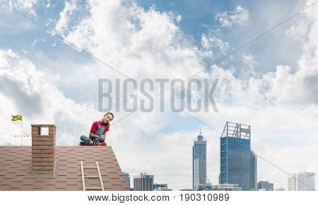Cute kid girl sitting on brick house roof and looking fearlessly down