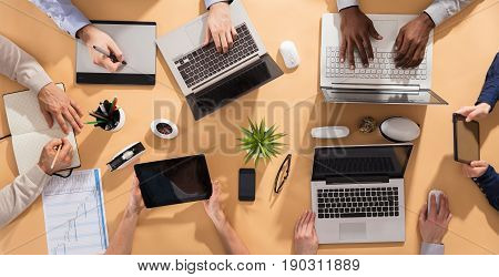 Overhead View Of Businesspeople's Hand Working On Office Desk With Laptop And Digital Tablet