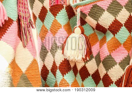 OTAVALO, ECUADOR - MAY 17, 2017: Beautiful andean traditional clothing textile yarn and woven by hand in wool, colorful fabrics background.