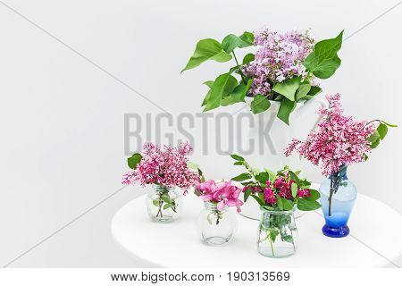 Bouquets of pink and purple spring flowers on a white table.
