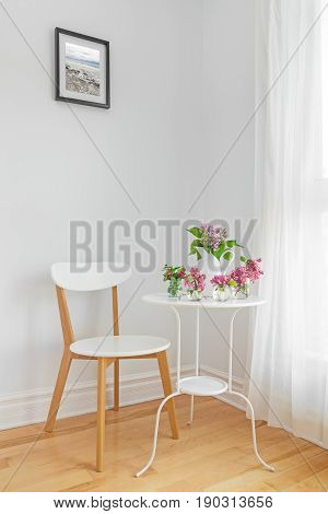 White interior with modern furniture and spring flowers. Elegant home decor.