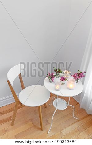 Elegant home interior with white chair and table decorated with candle lights and spring flowers.