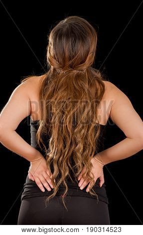 Close up of a young beautiful sportwoman suffer cervical pain in her lower back, in black background.