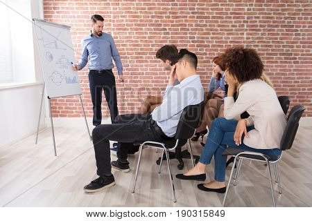 Businessman Giving Presentation To His Bored Colleagues In Office