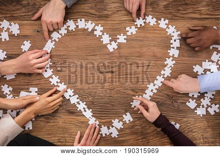 High Angle View Of Businesspeople Forming Heart Shape Sign With Jigsaw Puzzle