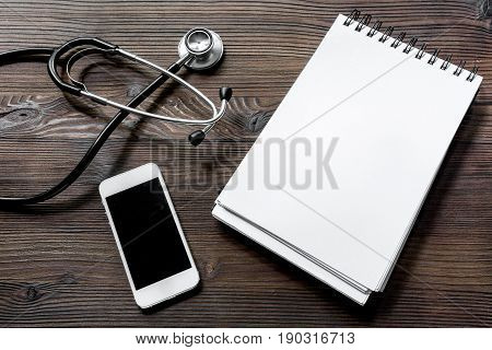 Make an appointment with doctor by phone dark wooden desk top view notebook.