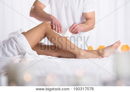 Therapist Waxing Woman's Leg With Wax Strip In Beauty Spa