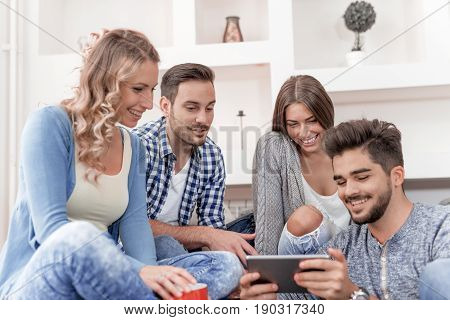 Group of trendy friends having fun in home living room.