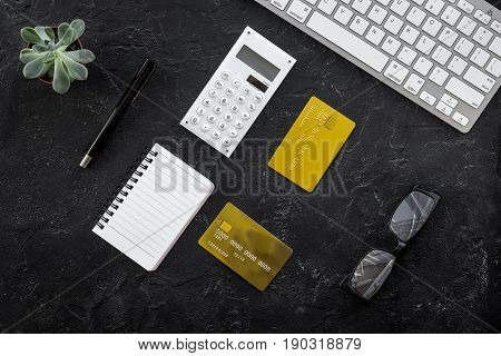 business purchasing with credit cards, keyboard and notebook on banker work desk dark background top view space for text