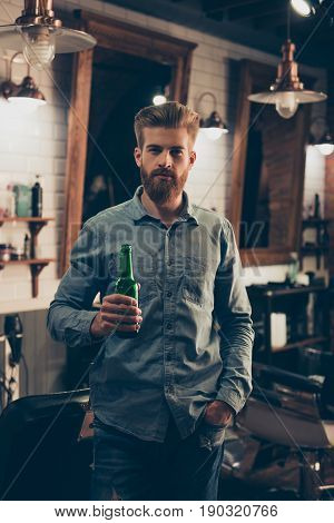 Casual Men`s Life. Attractive Stylish Young Red Bearded Man In A Casual Jeans Outfit Is Drinking Bee