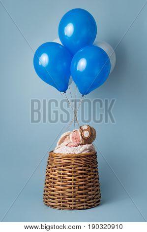 Sleeping nine day old newborn baby boy wearing an aviator hat and sleeping in a pretend hot air balloon.